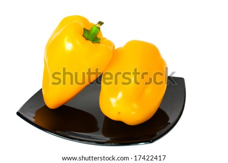 two yellow peppers on black plate