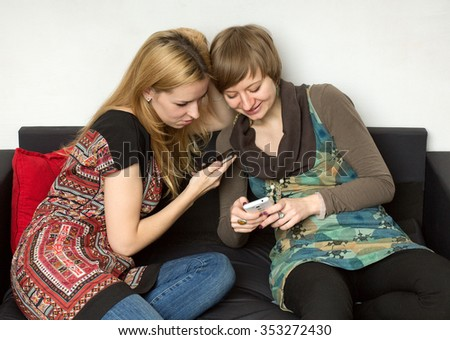 Two yong women in bright dresses are sitting on the black sofa with cellphones, looking at the screens, close up - stock photo