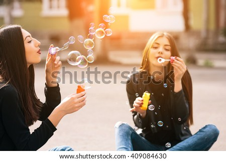 Two young adult girls sitting in a park and blow bubbles - stock photo