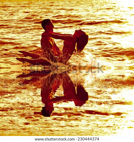 Two young adult lovers standing in water texture against  horizon beach and looking to each other on Vis a vis sunset background Wet body embracing and make sex in empty space for inscription  - stock photo