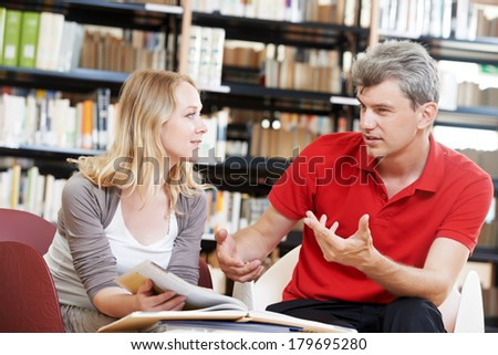 Two young adult peoples reading discussing book in a library - stock photo