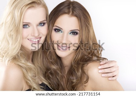 Two young adult smiling attractive sensuality and pretty girl friends - blond and brunette on white background - stock photo