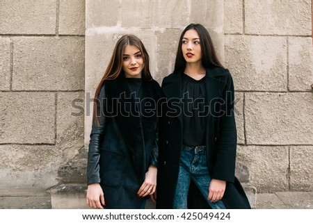 Two young adult women posing on a city street