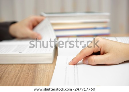 two young adults are studying and reading book - stock photo