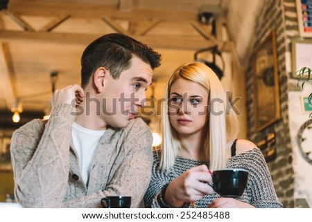 Two young adults in a cafe making some decisions. Natural light, narrow depth of field. - stock photo