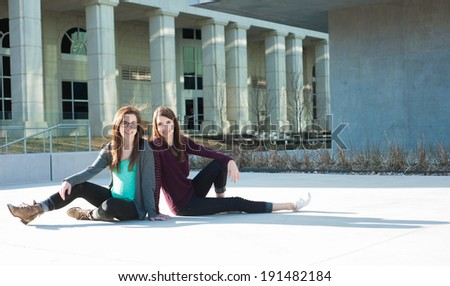 Two young adults outside on campus smiling - stock photo