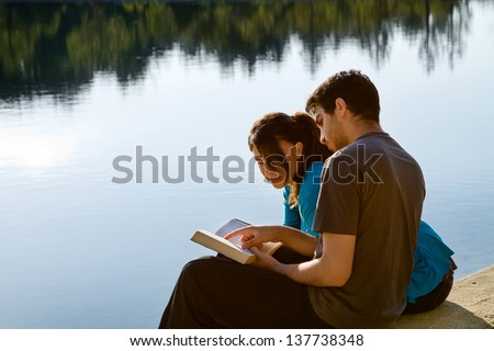 Two young adults sitting by a lake and studying the Bible (King James Version) - stock photo