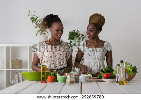 Two Young African Women Cooking. Healthy Food - Vegetable Salad. Diet. Dieting Concept. Healthy Lifestyle. Cooking At Home. Prepare Food - stock photo