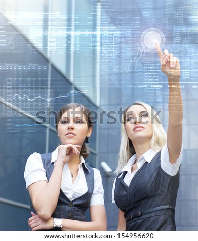 Two young and attractive business women working with a futuristic virtual display (business people in futuristic interface concept) - stock photo