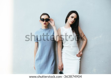 Two young and beautiful girl posing on a white background - stock photo