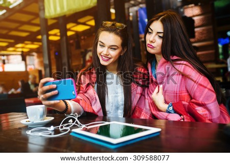 Two young and beautiful girl sitting at the table and doing selfie in the cafe