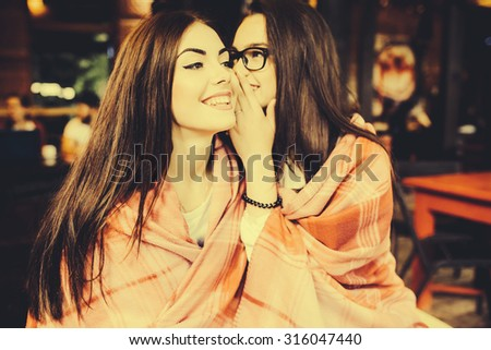 Two young and beautiful girls share secrets in cafe - stock photo
