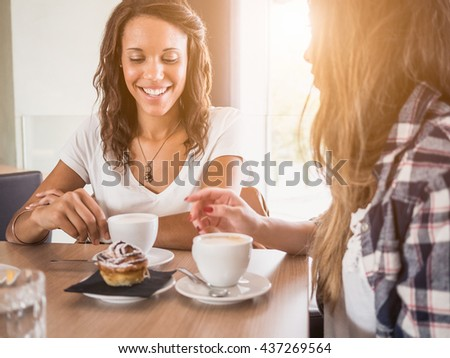 Two young and beautiful women meet at the bar for a cappuccino and to chat. A woman speaks gesturing while the other is listening - stock photo