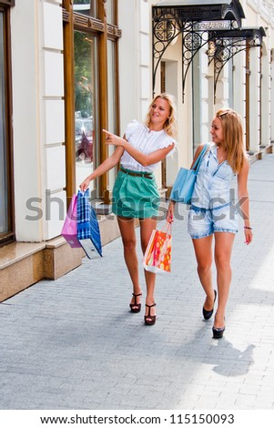 Two young and beautiful women walking down the street with shops