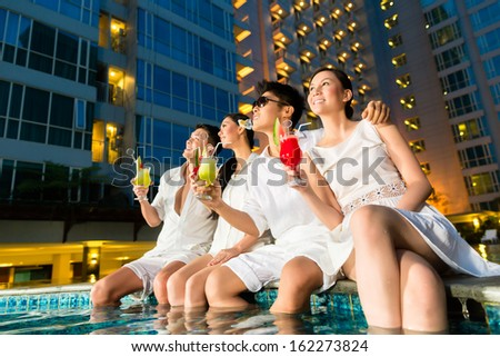 Two young and handsome Asian Chinese couples or friends drinking cocktails in a luxurious and fancy hotel pool bar  - stock photo