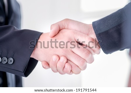 Two young and successful businessmen rejoice in the success of their language matters. Handsome young men shake their hands. Confident men smiling in formal suit