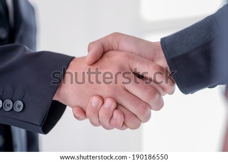 Two young and successful businessmen shake their hands and  rejoice in the success of their language matters. Handsome young men shake their hands. Confident men smiling in formal suit