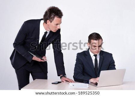 Two young and successful businessmen sitting at table and talking in office. Handsome men are sitting at laptop working on the tablet.Confident businessmen smiling  in formal wear and writing on paper