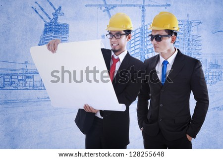 Two young architects are reviewing blueprint plan - stock photo