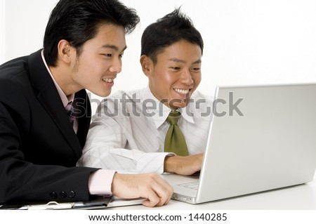 Two young asian businessmen working on a laptop computer
