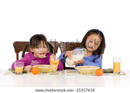 Two young Asian Girls eating a healthy Breakfast - stock photo