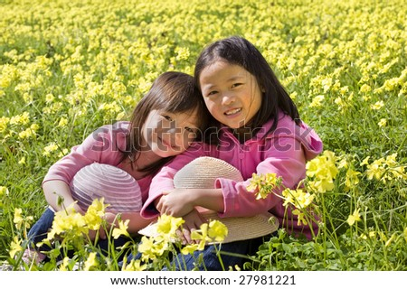 Two young asian girls in a yellow flower field - stock photo