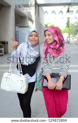 Two young asian muslim business student in head scarf smile while walking - stock photo