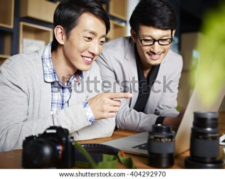 two young asian photographers designers selecting pictures using laptop computer in studio. - stock photo