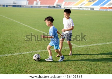 Two Young Asian play football in the grass football field in the stadium during summer. - stock photo