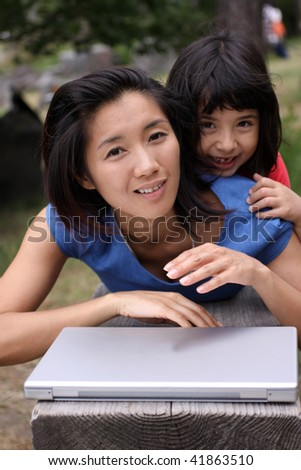 Two young Asian sisters playing with a laptop outside on a bench