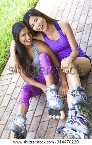 Two young Asian women girls, Chinese and Indian, laughing having fun in line roller skating - stock photo