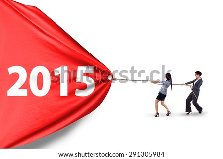 Two young asian women pulling number 2015 in studio, isolated over white background - stock photo