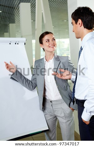 Two young associates by whiteboard looking at one another while communicating