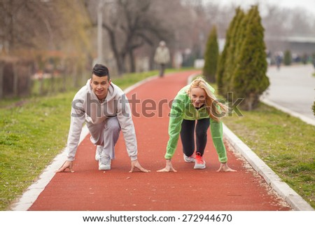 Two young athletes ready to start a race - stock photo