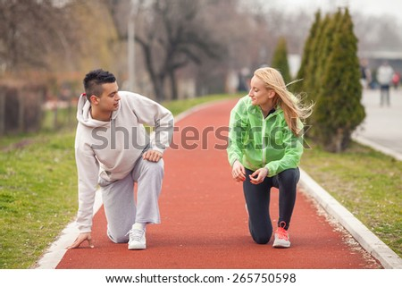 Two young athletes warming up for running - stock photo