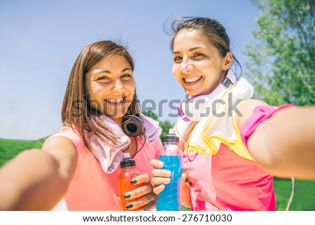Two young athletic women taking a picture after running in a park - Best friends training together outdoors,Both girls have towels, drinks and phone arm holder - stock photo