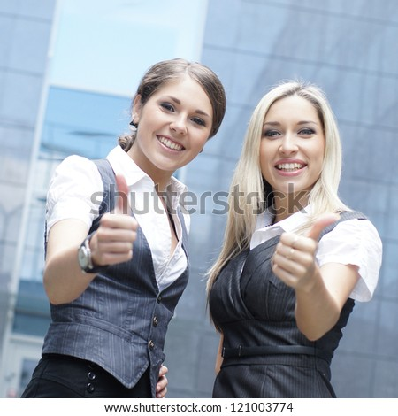 Two young attractive business women demonstrate the success - stock photo