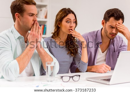 Two young attractive businessmen and one beautiful businesswoman in casual clothes using laptop and being upset while working in office