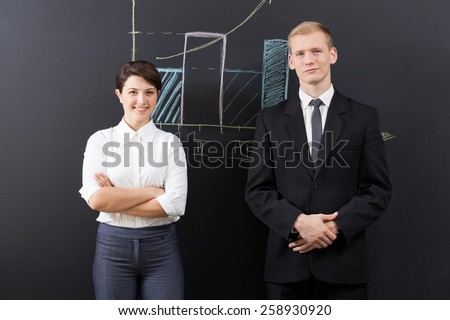 Two young attractive businesspeople in the office - stock photo
