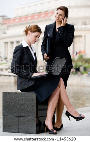 Two young attractive businesswoman working outside by Singapore river - stock photo