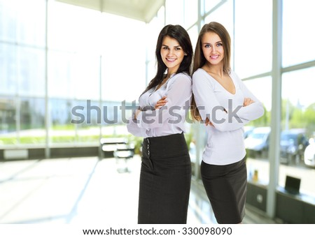Two young, attractive successful business woman stand with their backs to each other.