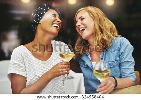 Two young attractive vivacious multiethnic female friends celebrating and laughing together over a glass of white wine - stock photo