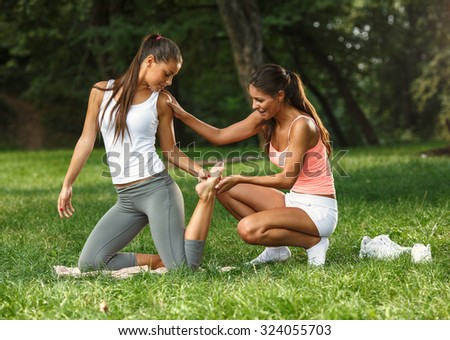 Two young attractive woman doing yoga in nature