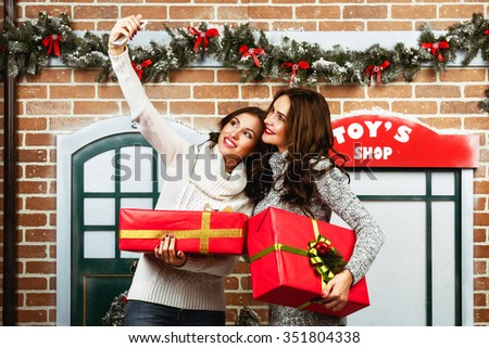 Two young attractive woman holds presets boxes in hands and making selfie on christmas street backdrop - stock photo