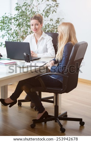Two young attractive women sitting in the office - stock photo