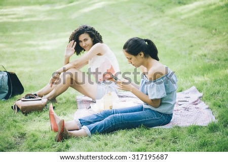 Two young attractive women sitting on the picnic blanket, chatting with each other, having a good time together