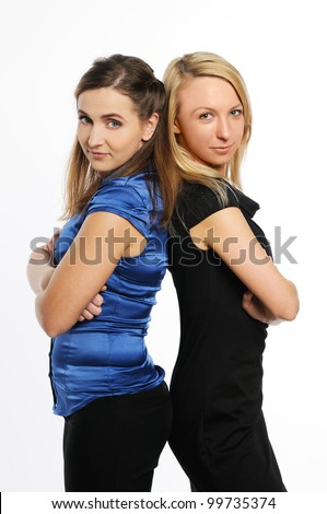 Two young attractive women standing back to back and look at the camera. - stock photo