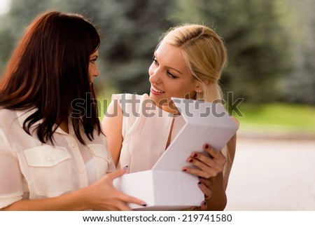 Two young attractive women talking about shopping. Blonde girl shows open box dark-haired girl - stock photo