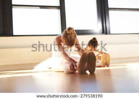 Two Young Ballerinas Doing an Exercise, Especially for their Legs, Inside the Studio Before the Actual Dance Rehearsal. - stock photo