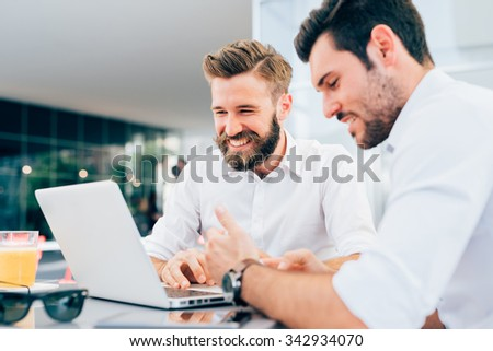 Two young bearded caucasian modern business man sitting in a bar, using laptop, looking downward, tapping on keyboard  - business, work, technology concept - focus on blonde hair man